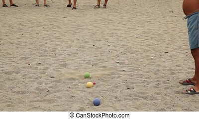 Five men in flip-flops throw balls by turns on beach - five...
