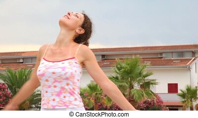 Woman in tank top enjoying of nature turns here and there -...