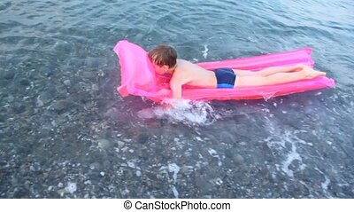 Boy floats on pink air bed by sea downwards