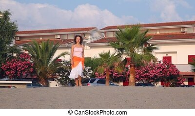 Brunette woman goes towards beach - brunette woman in white...