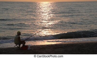 Man fishes and observes of sunset while sitting on coast