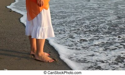 Woman in white douses barefoot feet in waves - woman in...
