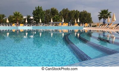 Water pool against chaise lounges and beach umbrellas -...