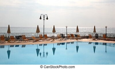 Morning sea landscape from pool and chaise lounges side -...