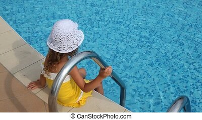 Girl sits on border of pool and douses her feet in water -...