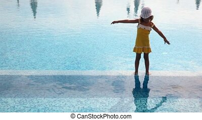 Girl stands in water in pool and with the lifted hands bends...