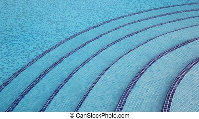 Six steps which leads on depth in pool laid out by mosaic at bottom