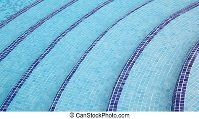 Steps on depth in pool that laid out by mosaic at bottom -...