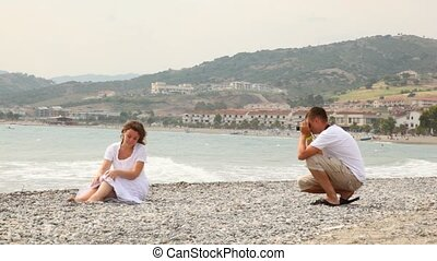 Man in shorts photographed woman on rocky beach - man in...