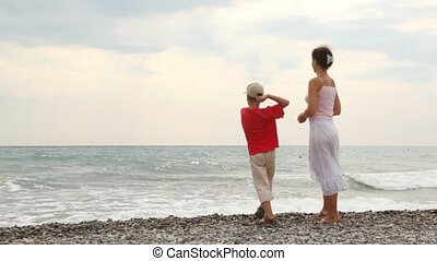 Mother and son stand on sea coast and throw pebbles - mother...