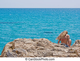 Lonely girl on the rock at sea shore
