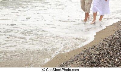 Male and female feet walk on coast