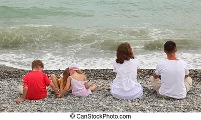 Father mother and children have rest on seacoast - father...