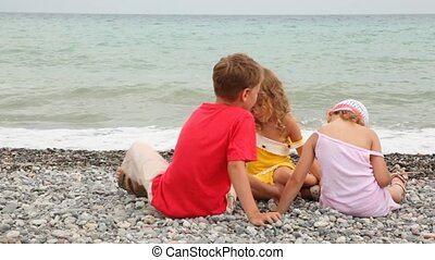 Boy and girls play on stony seacoast - boy and two girls...