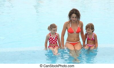 Woman with two daughters communicate in pool