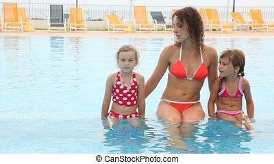Woman says something with two daughters in pool - young...