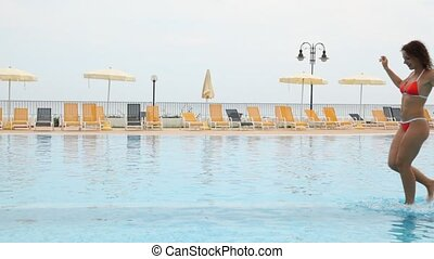 Woman run along pool in front of chaise longue and beach...