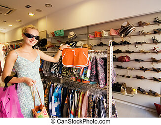 Blong girl buying clothes in a shop