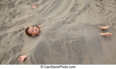 Boy lies smiles buried up with sand on beach - top view of...
