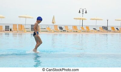 Boy in bathing cap slide down in pool - boy in blue swimming...