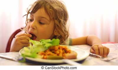 Girl in dining room hands eats leaf of lettuce, pizza - girl...