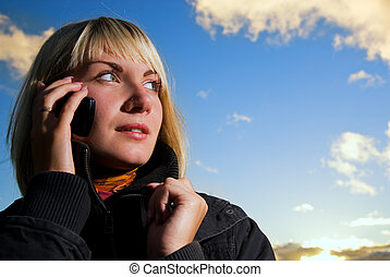 Blonde girl tolking on the cell phone over blue cloudy sky