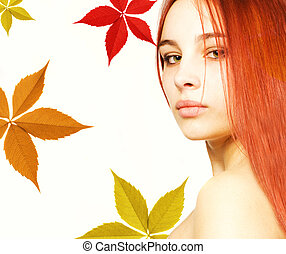 Beautiful girl with a red hair and colorful autumn leaves...