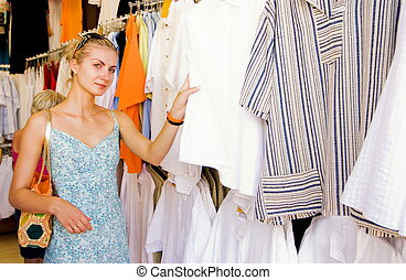 Blond girl buying clothes in a shop
