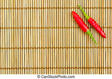 Red chilli on a bamboo mat - Two red chilli at the right...