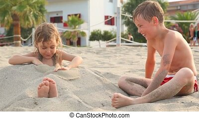 Playing elder brother falls up with sand his sister tries...