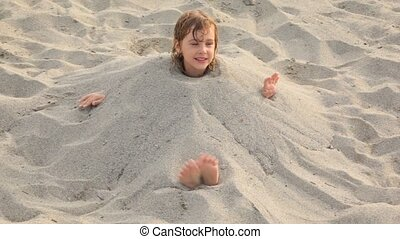 Little girl sits filled up with sand on neck on beach -...