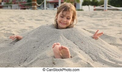 Little girl smiles siting filled up with sand on neck on...