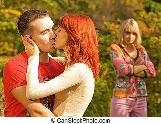 Young couple kissing and offended girl standing on a...