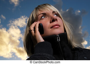 Girl talking to the phone over blue cloudy sky