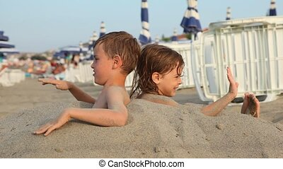 Brother and sister sit on beach buried on breast in sand -...