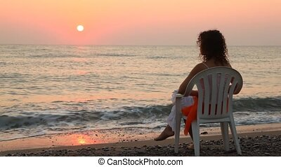 Woman sits on chair alone on beach faced to sea at sunset