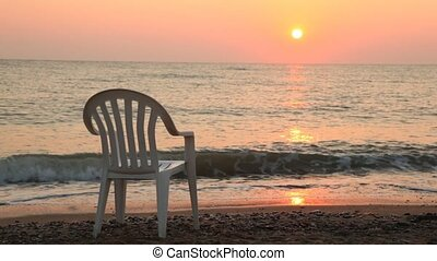 White chair there is on beach in front of sea at sunset -...