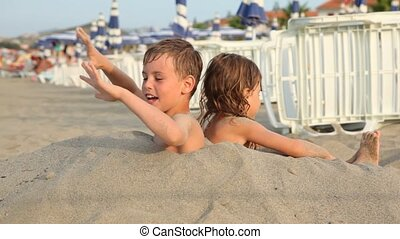 Brother and sister try to stand up buried on breast in sand...
