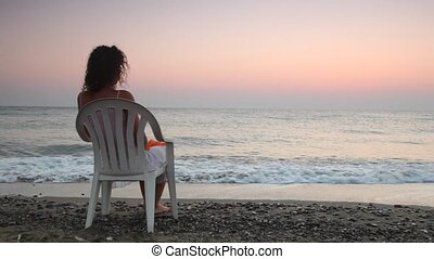 Woman sits on plastic chair alone on beach faced to sea