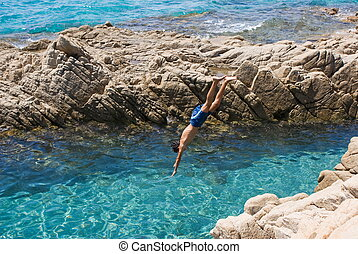 Plunge of a young boy from a cliff in a beautiful blue sea