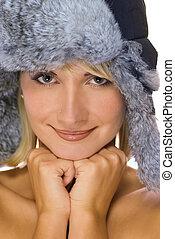 Beautiful young girl in winter fur-cap