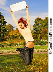 Beautiful redhead girl jumping with a white noticeboard on autumn