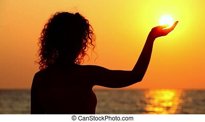 Young woman standing on beach, watching sunset