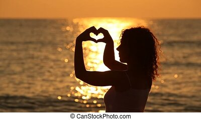 Woman stands on beach and shows heart form with hands help against sunset