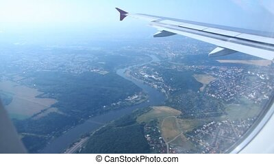 View from window on wing of plane flying over Prague and river Vltava