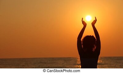 Woman standing on beach, holding sun in her hands