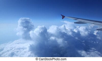 Wing of plane against blue sky - white wing of plane against...