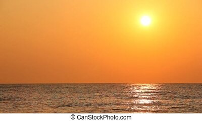 Sunset against orange sky over quiet sea waves - beautiful...