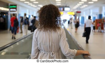 Woman moving on speedwalk at airport - Curly-headed woman in...