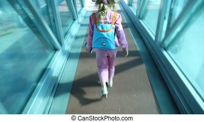 Girl goes on crossing with glass walls at airport - girl in...